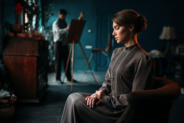 Beautiful woman poseur, painter draws a portrait on easel.