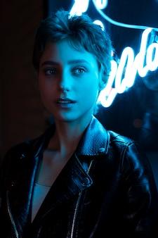 青いネオンの光の中で夜にポーズをとって美しい女性