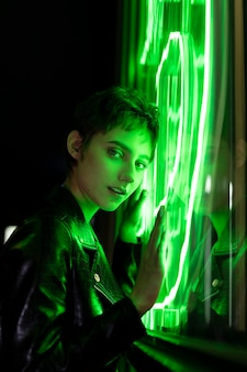緑のネオンの光で夜にポーズをとって美しい女性
