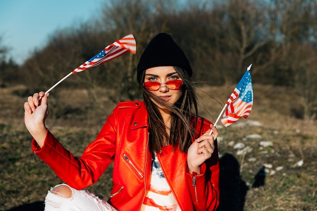 Beautiful woman posing and holding american flags