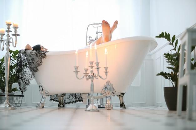 Bella donna che posa a casa nel bagno