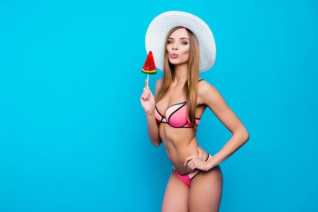 Красивая женщина позирует в бикини и шляпе