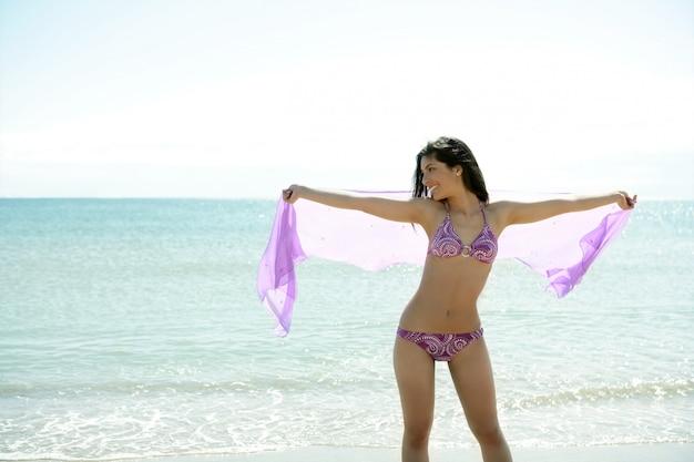 美しい女性がビーチでビキニでポーズ