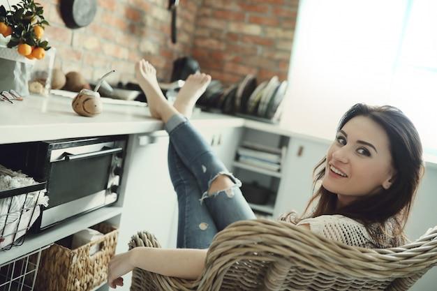 Красивая женщина позирует в кресле у себя дома Бесплатные Фотографии