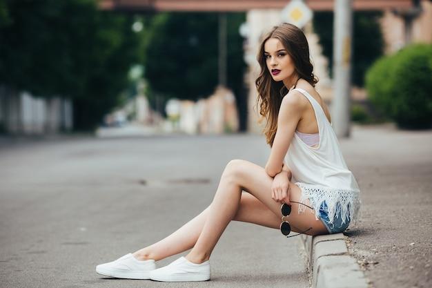 거리에 도시에서 포즈를 취하는 아름 다운 여자