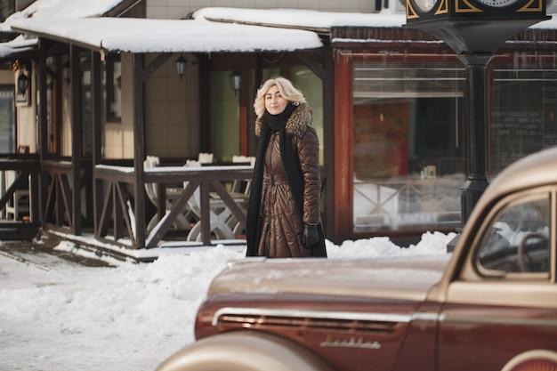 街で冬のポーズをとる美しい女性。