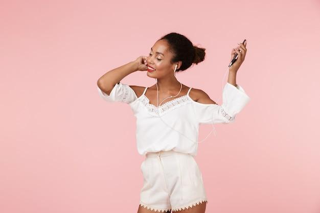踊るイヤホンで音楽を聴いてピンクの壁に孤立したポーズの美しい女性