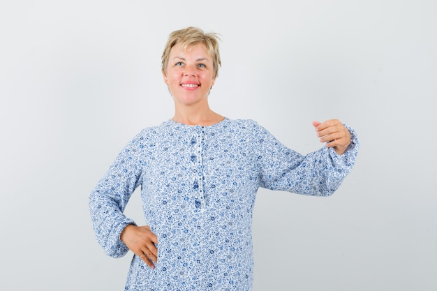 Beautiful woman posing like holding hand someones shoulder in patterned blouse and looking photogenic , front view.