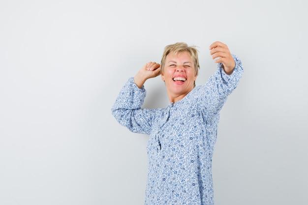 Bella donna in posa come prendere selfie in camicetta fantasia e sembra pazza. vista frontale.