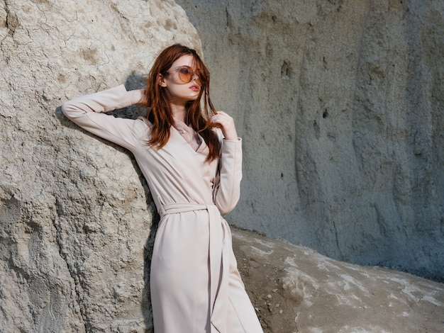 砂のライフスタイルファッションで岩の近くでポーズをとる美しい女性