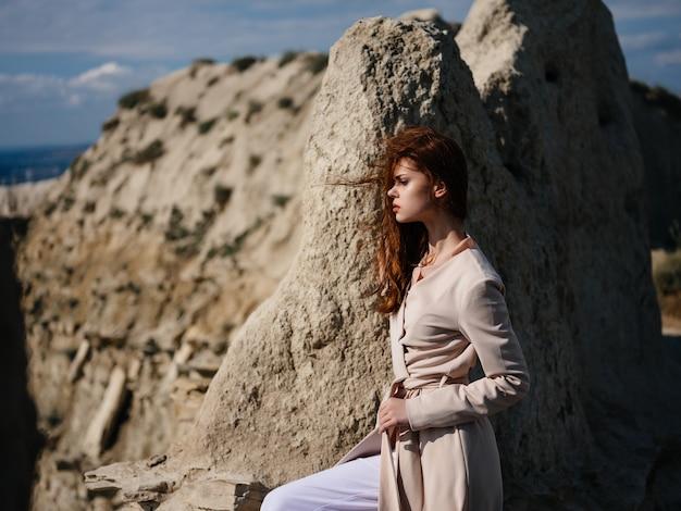 砂モデル旅行で岩の近くでポーズをとる美しい女性
