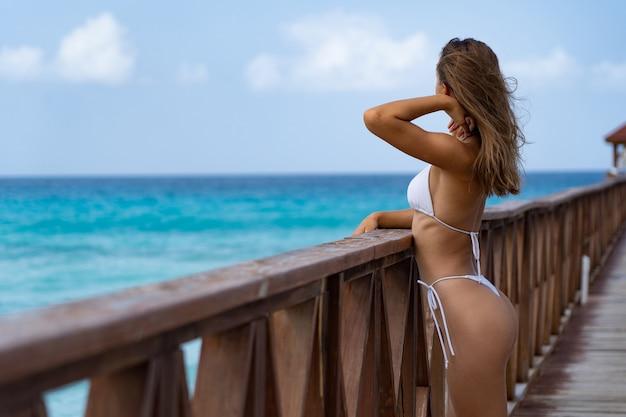 흰색 비키니를 입고 열 대 해변에서 부두에 포즈를 취하는 아름 다운 여자. 휴가 및 여행 개념입니다. 고품질 사진