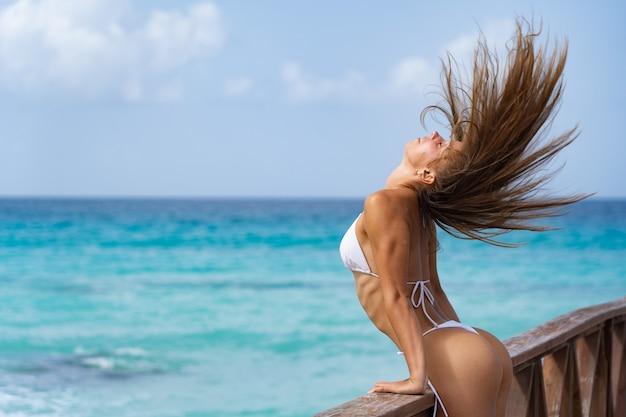 흰색 비키니에 열 대 해변에서 부두에서 포즈를 취하는 아름 다운 여자.