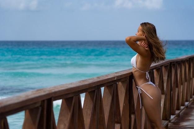 흰색 비키니 럭셔리 휴가 컨셉으로 푸른 물이 있는 부두에서 포즈를 취하는 아름다운 여성