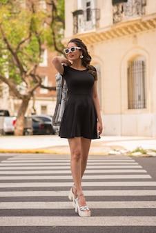 街の通りでポーズをとって美しい女性