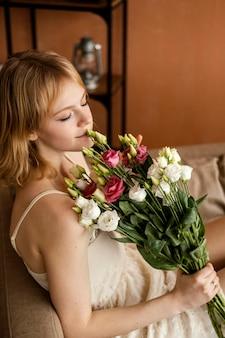 春の花の花束を保持しながらソファでポーズをとる美しい女性