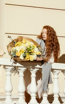 봄 꽃의 부케와 함께 야외에서 포즈를 취하는 아름 다운 여자