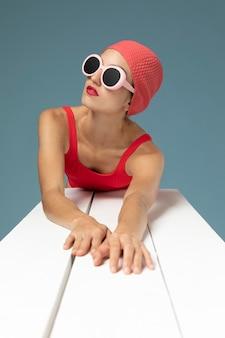 Bella donna che posa in un costume da bagno rosso