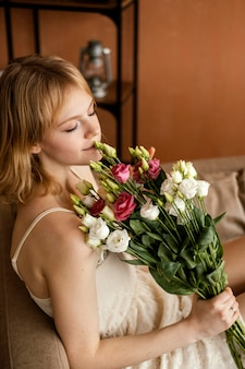 Bella donna in posa sul divano mentre si tiene il mazzo di fiori primaverili
