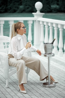 Beautiful woman posing in sunglasses sitting in a chair in the fresh air