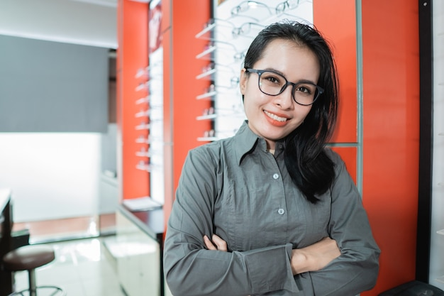 A beautiful woman posing wearing glasses against the background of an eyeglass display case in an eye clinic