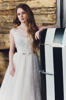 The beautiful woman posing in a wedding dress.