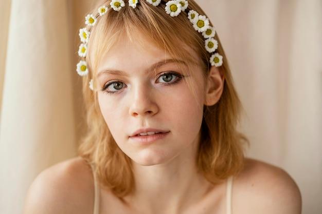 Bella donna in posa mentre indossa una bella corona di fiori primaverili