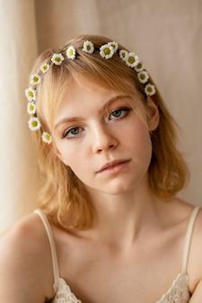 Bella donna in posa mentre indossa una delicata corona di fiori primaverili