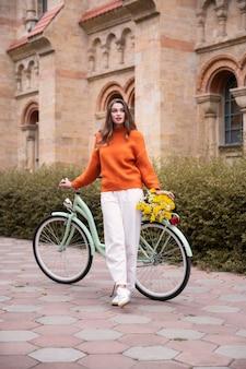 Bella donna in posa con la bicicletta e fiori all'aperto