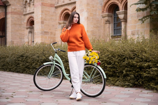 Beautiful woman posing with bicycle and flowers outside