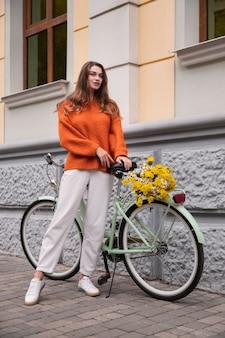 야외에서 자전거와 함께 포즈를 취하는 아름 다운 여자