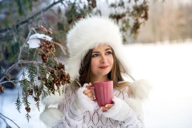 겨울 공원에서 컵과 함께 포즈를 취하는 아름 다운 여자