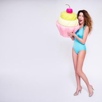 灰色の背景の上の巨大なカップケーキでポーズをとって美しい女性