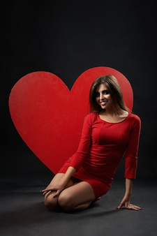 Beautiful woman posing with giant heart at the studio