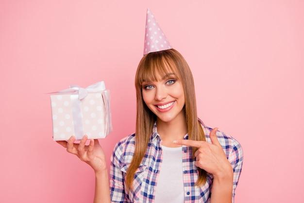 ピンクの壁にギフトボックスでポーズをとって美しい女性