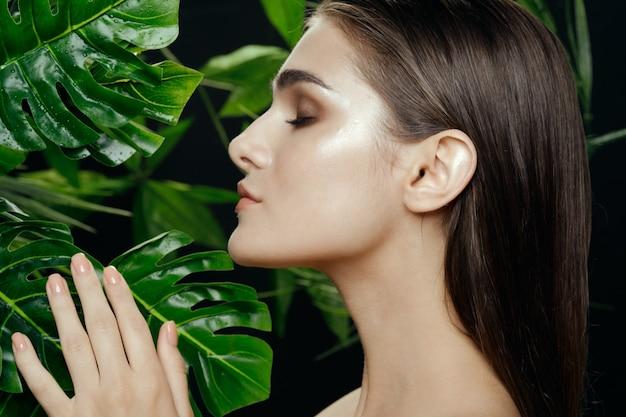 Красивая женщина позирует с зелеными листьями монстеры