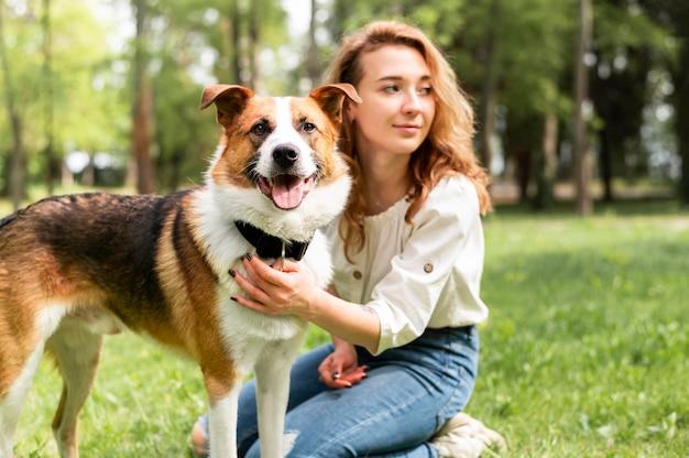 美しい女性が彼女の犬と一緒にポーズ