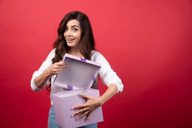 보라색 선물 상자와 함께 포즈를 취하는 아름 다운 여자. 고품질 사진