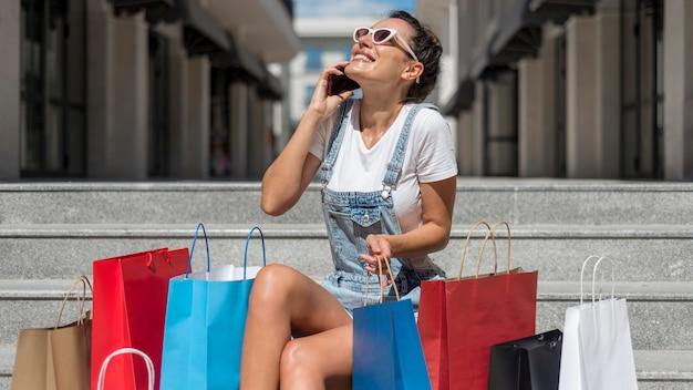 Красивая женщина позирует с хозяйственными сумками