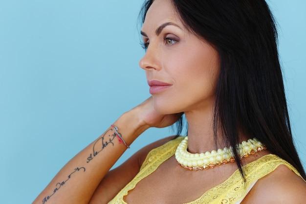 黄色のtシャツでポーズをとって美しい女性