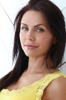 Красивая женщина позирует с желтой футболкой