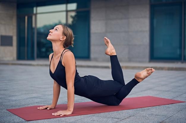 Beautiful woman practices yoga asana ardha bhujangasana - half cobra pose outdoors