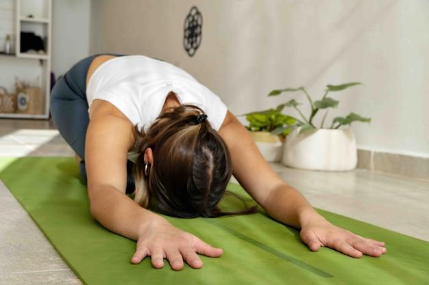 Красивая женщина практикует асану йоги баласана - поза ребенка в студии йоги с растениями