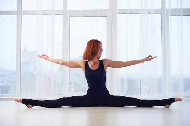 Красивая женщина занимается йогой асаны самаконасана прямоугольная осанка в студии йоги.