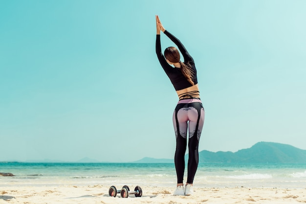 Beautiful woman practices yoga by the sea on a sunny day. the woman does stretching exercises. dumbbells lying sand. back view