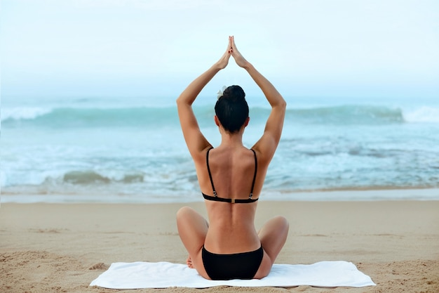 Beautiful woman practices yoga and meditates in the lotus position on th ebeach. girl doing yoga.