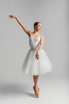 Bella donna che pratica colpo pieno di balletto