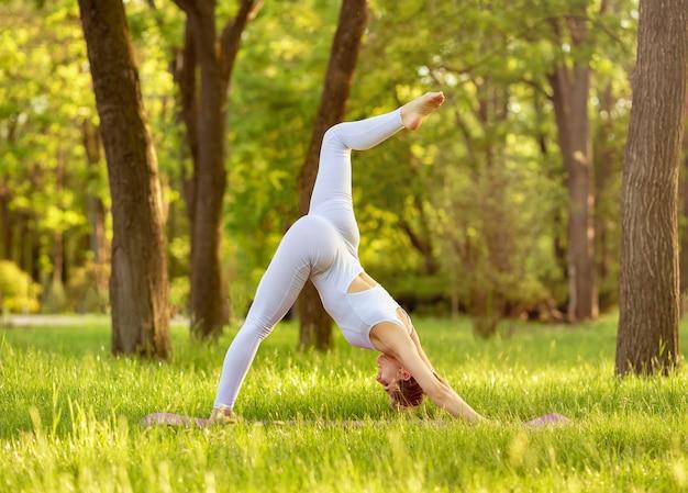 朝の光の中でヨガを練習している美しい女性。ヨガのポーズ。