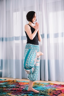 Beautiful woman practicing yoga and meditation at home