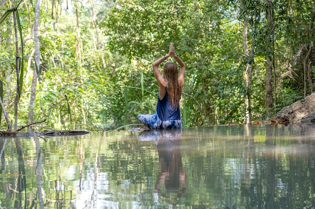 Beautiful woman practicing yoga near forest lake. young woman near turquoise water of cascade waterfall at deep tropical rain forest, island koh phangan, thailand